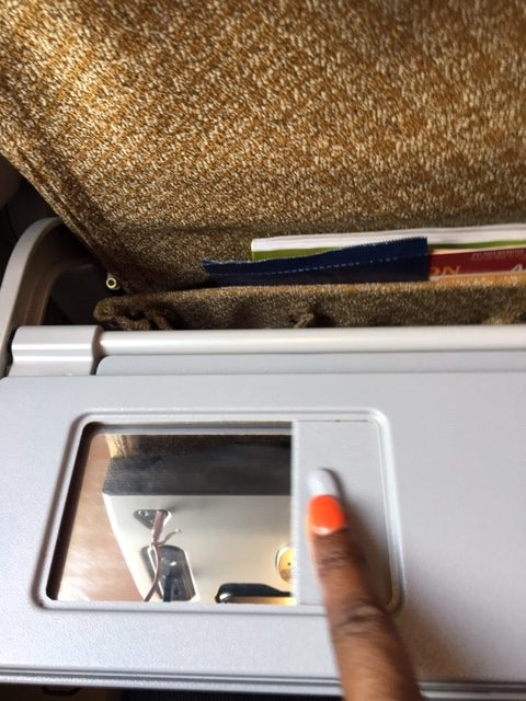 A vanity mirror embedded in the seat back tray of seats in Singapore Airlines economy class.