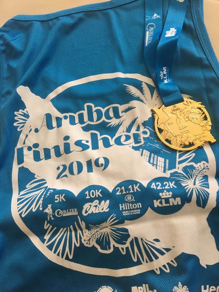 Finisher's medal and shirt from the KLM Aruba Marathon