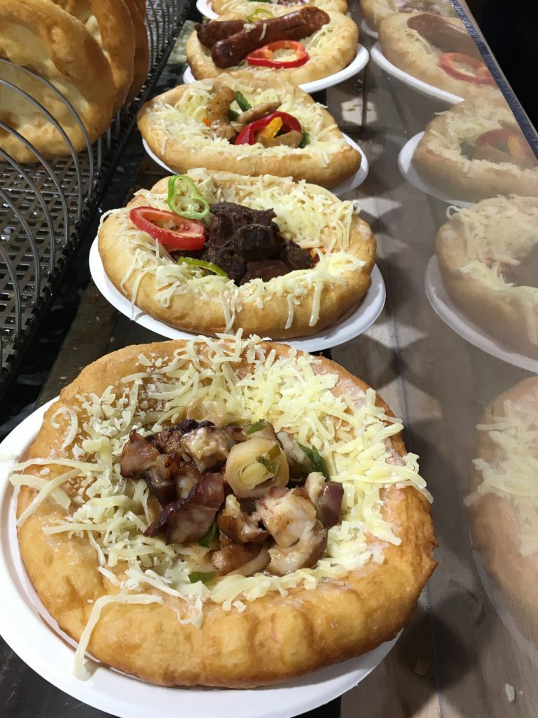 Hungary's legendary street food, Lángos, is deep-fried flatbread topped with sour cream and grated cheese and followed by anything else, such as meat, onions, cabbage...whatever your tastebuds desire. Photo credit: Monique White