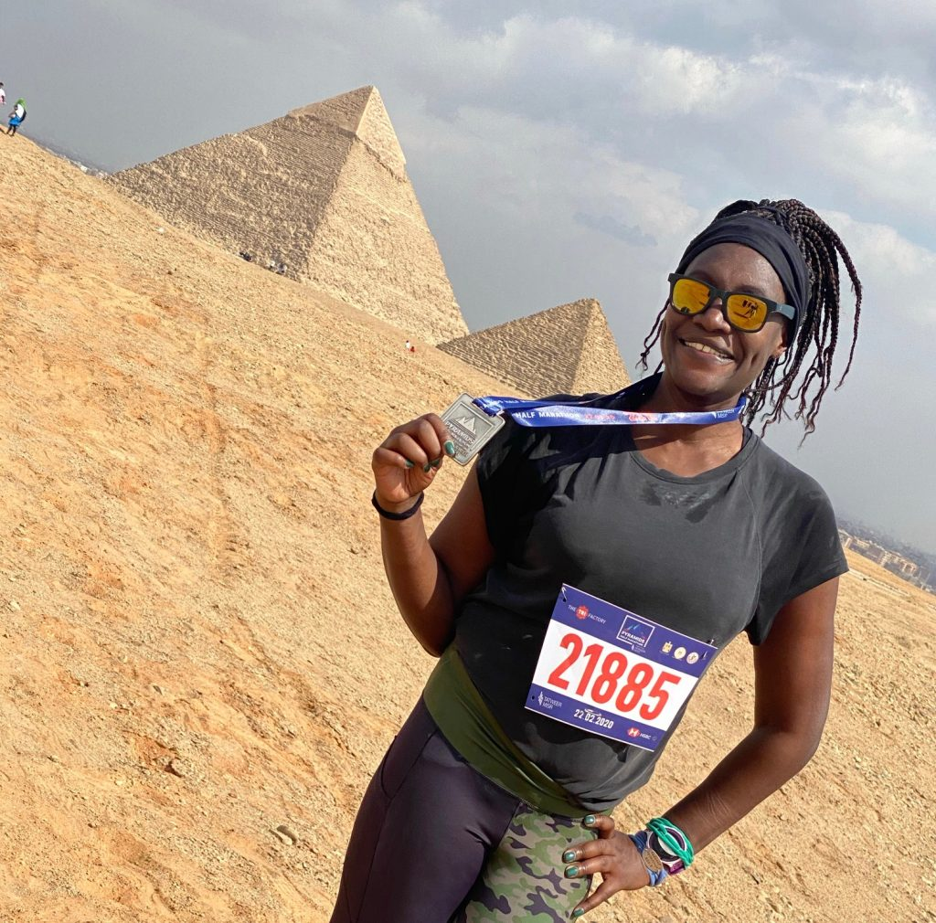 With a medal after finishing the Pyramids Half Marathon, which marked country # 42 of #MoniqueRuns50! Photo credit: Monique White